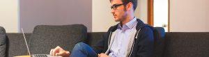 Hombre joven consultando su ordenador portátil en el salón
